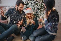 Familia joven hermosa que disfruta de su tiempo del día de fiesta junto, adornando el árbol de navidad, arreglando las luces de l Foto de archivo libre de regalías