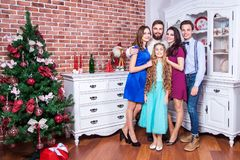 Familia joven hermosa que disfruta de tiempo de la Navidad y que abraza con amor Imagen de archivo