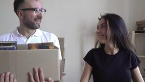 Familia joven móvil El marido y la esposa están en las manos de una caja de libros y de cosas Un par joven se mueve alrededor de almacen de video