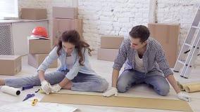 Familia joven ocupada con la reparación de su nuevo apartamento almacen de metraje de vídeo