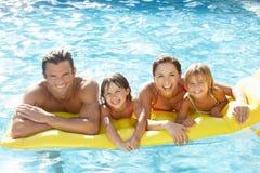 Familia joven, padres con los niños, en piscina fotografía de archivo
