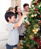 Familia joven que adorna un árbol de navidad Imagen de archivo libre de regalías