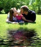 Familia joven que besa al bebé por W Imágenes de archivo libres de regalías