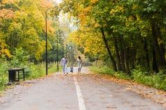 Familia joven que camina en el parque al día del otoño Imagen de archivo