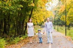 Familia joven que camina en el parque al día del otoño Foto de archivo libre de regalías