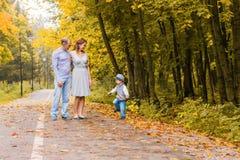 Familia joven que camina en el parque al día del otoño Fotografía de archivo libre de regalías