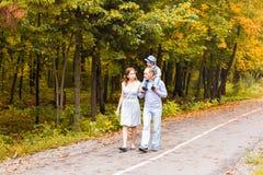 Familia joven que camina en el parque al día del otoño Imagenes de archivo