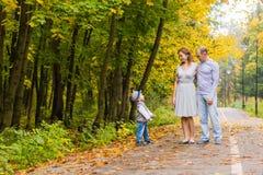 Familia joven que camina en el parque al día del otoño Imagen de archivo libre de regalías