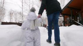 Familia joven que camina en el patio Un pequeño bebé que juega con nieve almacen de video