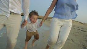 Familia joven que corre en la playa