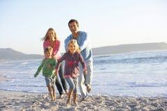 Familia joven que corre a lo largo de Sandy Beach On Holiday Imagenes de archivo