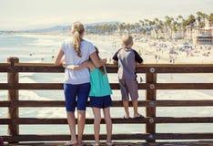 Familia joven que cuelga hacia fuera en un embarcadero del océano el vacaciones Fotografía de archivo