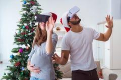 Familia joven que cuenta con al bebé del niño que lleva gla de la realidad virtual VR Foto de archivo libre de regalías