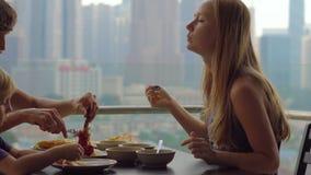 Familia joven que desayuna, almuerzo en su balcón en un rascacielos con una opinión sobre un centro de la ciudad del conjunto de  metrajes