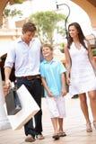 Familia joven que disfruta de viaje de las compras Imagenes de archivo