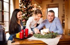 Familia joven que enciende velas en la guirnalda del advenimiento Árbol de navidad Imagen de archivo libre de regalías