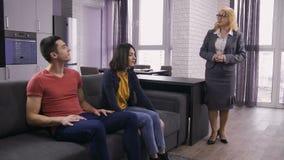 Familia joven que habla con el agente de la propiedad inmobiliaria en el sofá almacen de metraje de vídeo