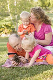 Familia joven que habla de conos del pino en parque foto de archivo