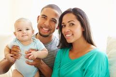 Familia joven que juega con el hijo feliz del bebé en casa Imágenes de archivo libres de regalías
