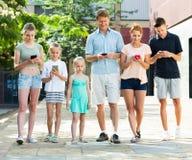Familia joven que juega con los teléfonos móviles Imagenes de archivo