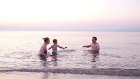 Familia joven que juega el barco rojo del juguete en la puesta del sol metrajes