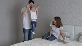 Familia joven que juega en cama en casa Juego de la mamá y del papá con su hija almacen de metraje de vídeo