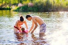 Familia joven que juega en el agua Fotografía de archivo libre de regalías