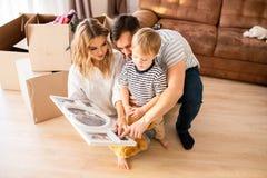 Familia joven que mira las fotos foto de archivo