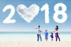 Familia joven que mira los números 2018 Imagen de archivo libre de regalías