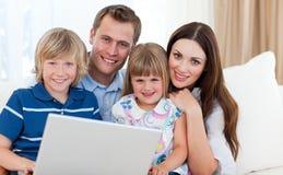Familia joven que practica surf el Internet Foto de archivo libre de regalías