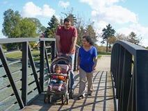 Familia joven que recorre en el puente. Foto de archivo libre de regalías