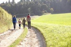 Familia joven que recorre en parque Imagen de archivo libre de regalías