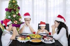 Familia joven que ruega antes de cena de la Navidad Fotografía de archivo