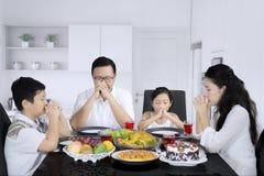Familia joven que ruega antes de comidas en la cocina Fotos de archivo libres de regalías