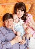 Familia joven que se acuesta y que sonríe Imágenes de archivo libres de regalías