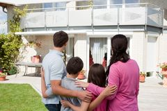 Familia joven que se coloca delante de su hogar ideal Fotos de archivo libres de regalías