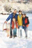 Familia joven que se coloca en el paisaje Nevado Foto de archivo