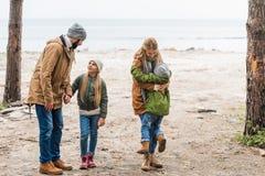 familia joven que se divierte en la costa en otoño frío imagenes de archivo