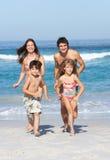 Familia joven que se ejecuta a lo largo de la playa el día de fiesta Fotografía de archivo libre de regalías