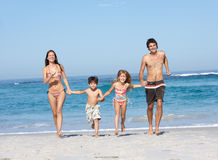 Familia joven que se ejecuta a lo largo de la playa el día de fiesta Imagen de archivo libre de regalías