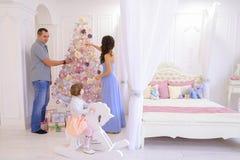 Familia joven que se prepara para próximo en luz espaciosa del dormitorio encendido Imagen de archivo libre de regalías