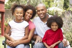 Familia joven que se relaja en jardín junto foto de archivo libre de regalías