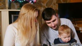 Familia joven que se sienta en casa acogedora Juegos del niño pequeño con los coches del juguete metrajes