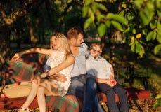 Familia joven que se sienta en el banco del jardín Imagenes de archivo