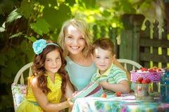 Familia joven que se sienta en la tabla en el jardín Imagen de archivo libre de regalías