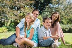 Familia joven que se sienta en un parque Fotos de archivo libres de regalías