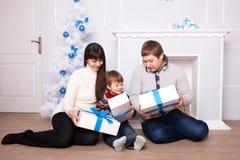 Familia joven que sostiene los regalos cerca de la chimenea Imagen de archivo libre de regalías