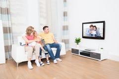 Familia joven que ve la TV junto Imagen de archivo libre de regalías