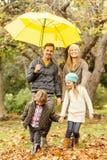 Familia joven sonriente debajo del paraguas Foto de archivo libre de regalías