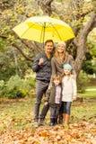 Familia joven sonriente debajo del paraguas Fotos de archivo
